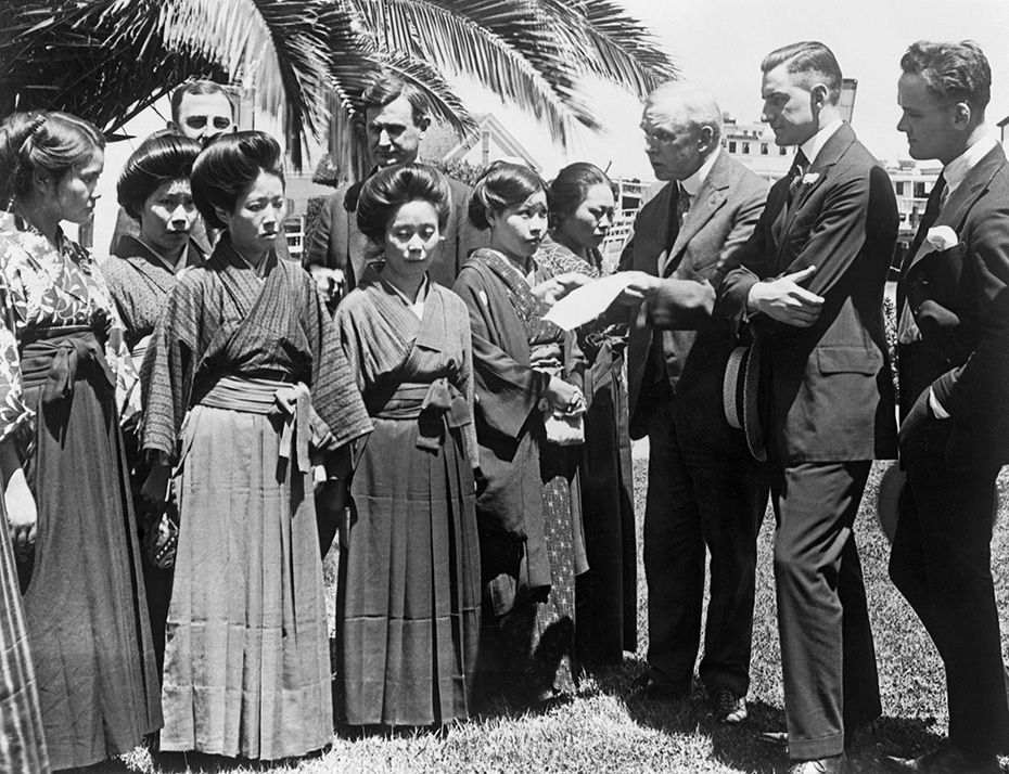 Black and white photograph of Japanese women in traditional kimonos (left) and white government officials (surrounding the women) reviewing their passports. The image was taken at Angel Island in 1920.